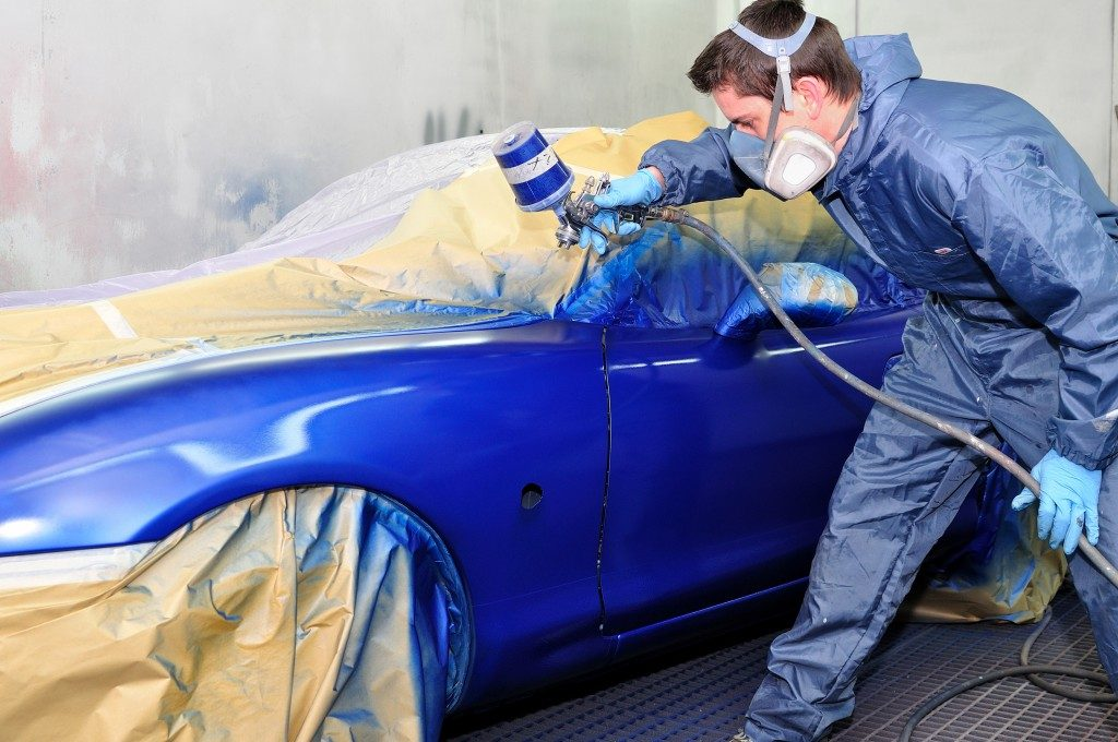 Worker painting the car blue