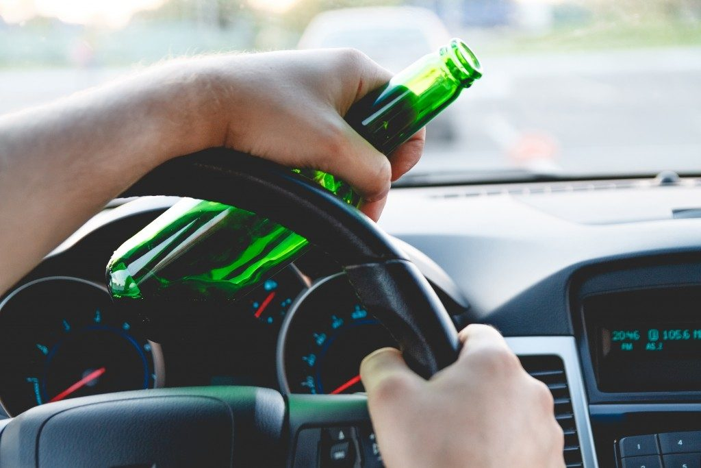 man driving while holding a bottle
