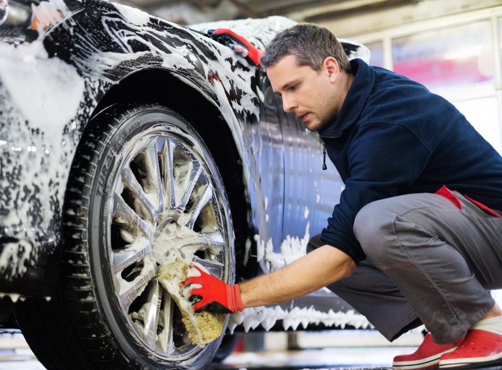 Man cleaning the car wheel