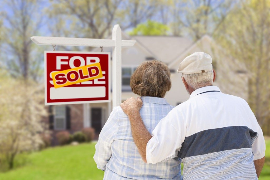 Senior Couple Hugging in Front of Sold Real Estate Sign and House