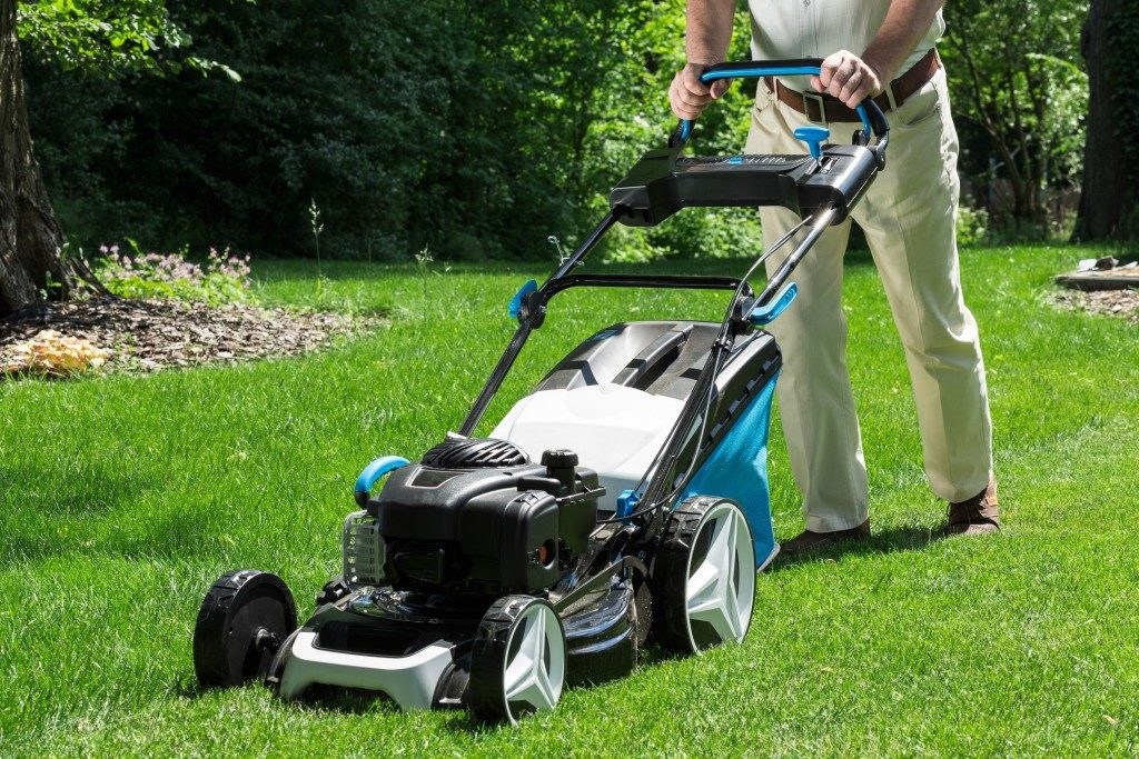 Lawnmower is being used by gardener