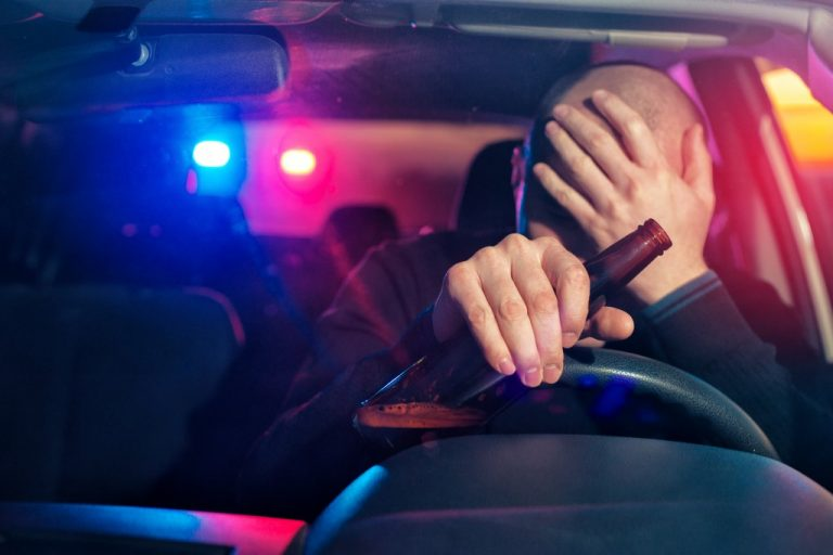 man caught driving under influence with police lights in the background