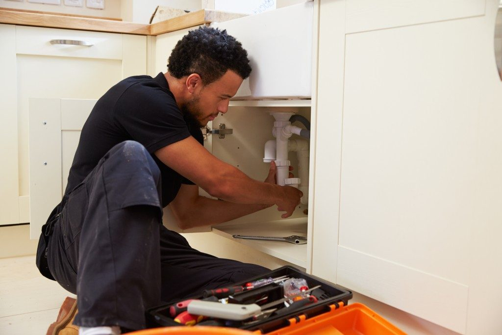 A man repairing a sink in their house