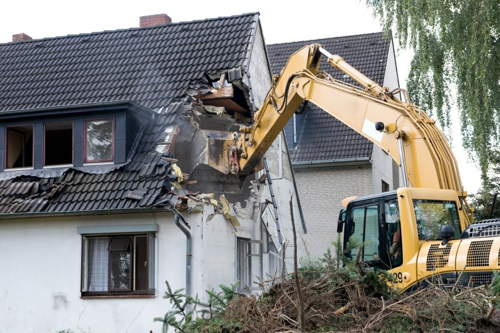 A digger demolishing houses for reconstruction