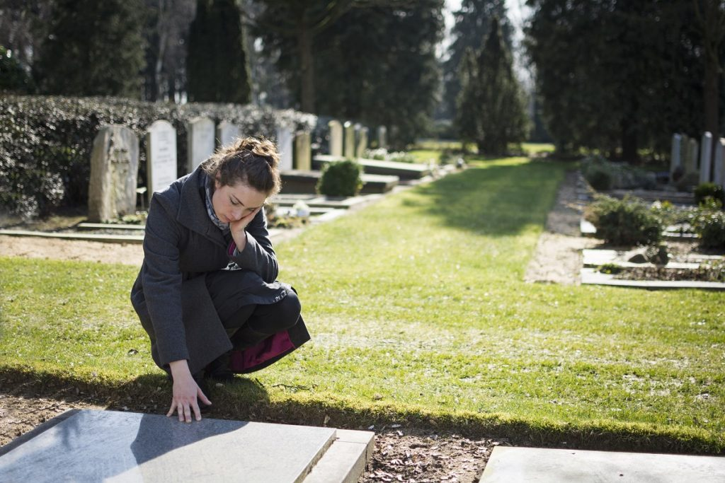 woman mourning for a loved one in the cemetery