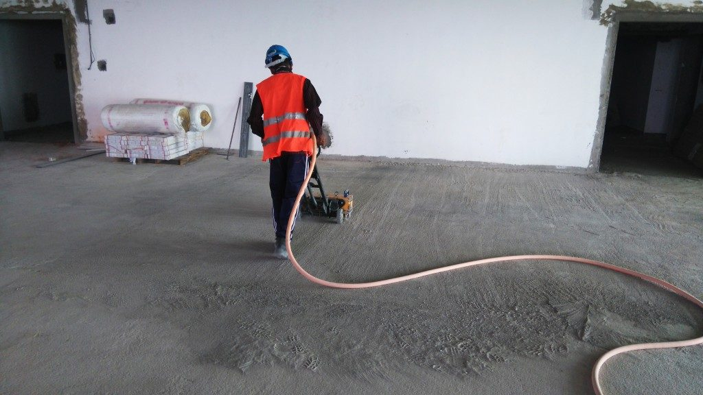 worker flattening concrete on the ongoing home construction