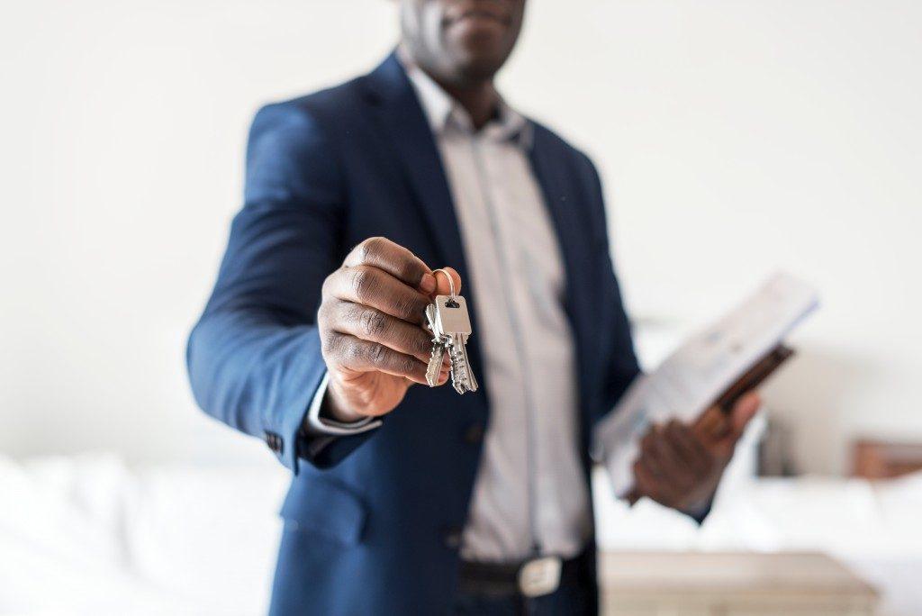 lower shot of an estate agent handing a home key