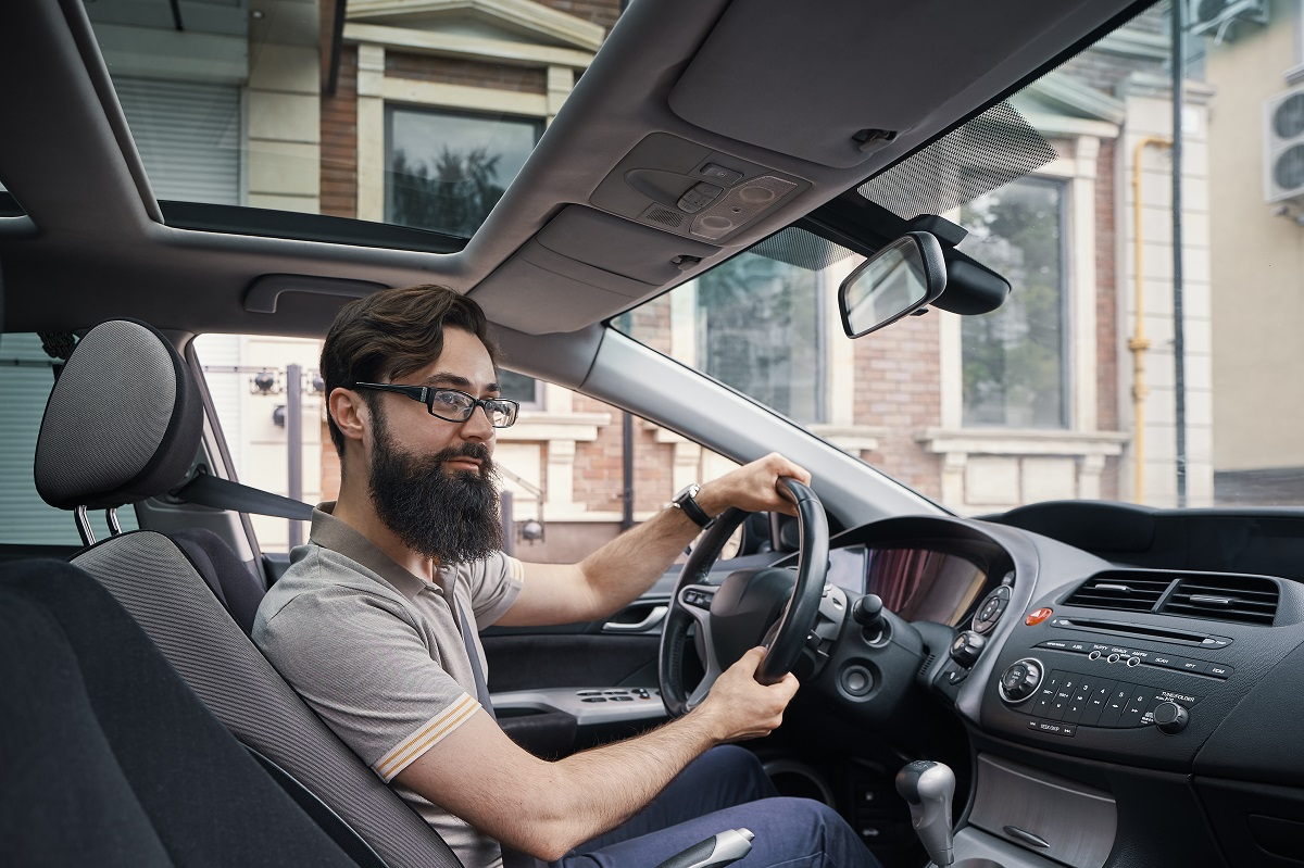 Happy charismatic man driving a car