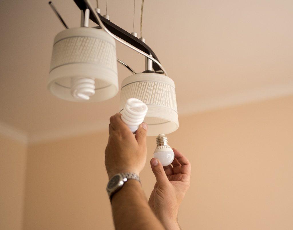 person installing led light bulbs