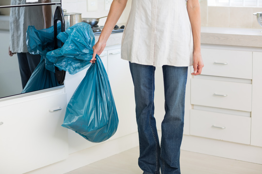 Woman carrying garbage bag in the kitchen at house