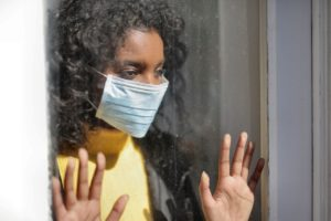 woman wearing facemask staring out the window