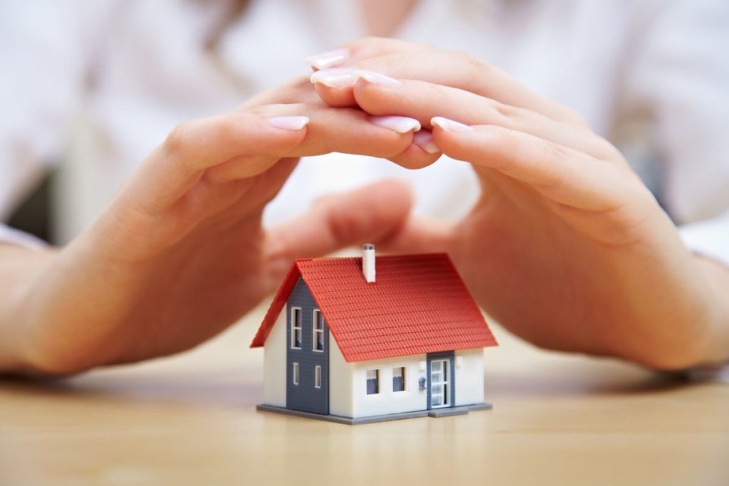 hands hovering over miniature house