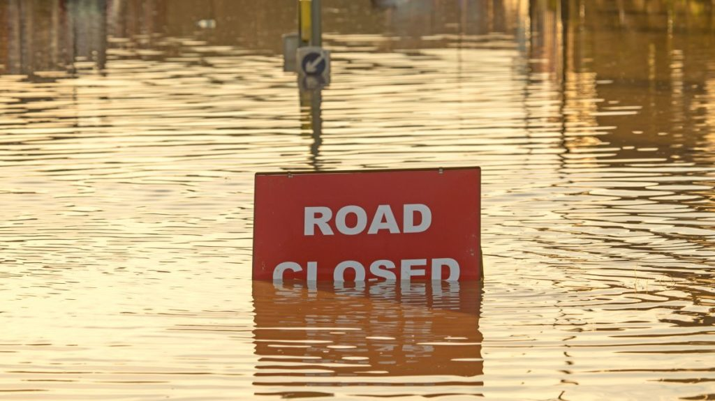 road closed sign submerged in flood