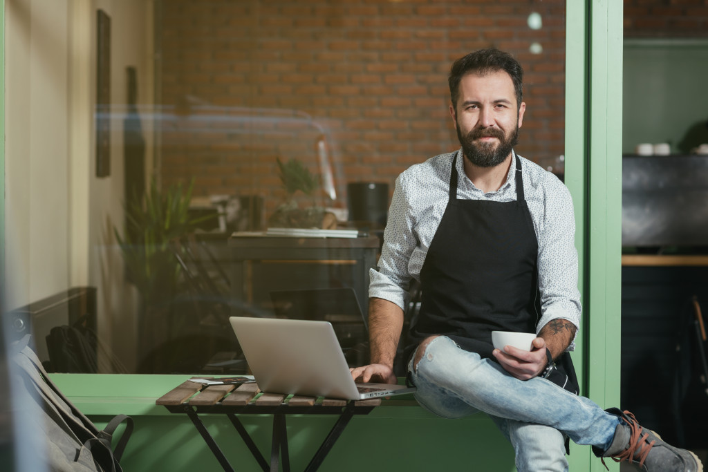 barista holding cup and laptop
